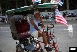 Un cubano exhibe una bandera de EEUU en su bicitaxi, en una calle de La Habana.