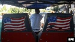 Un hombre conduce un bicitaxi en La Habana con banderas de Estados Unidos pintadas al fondo. EFE