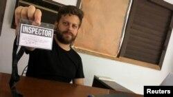 """El artista cubano Leandro Feal sostiene una tarjeta de presentación que dice: """"inspector"""", un performance que denuncia la figura de control artístico amparada bajo el Decreto Ley 349."""