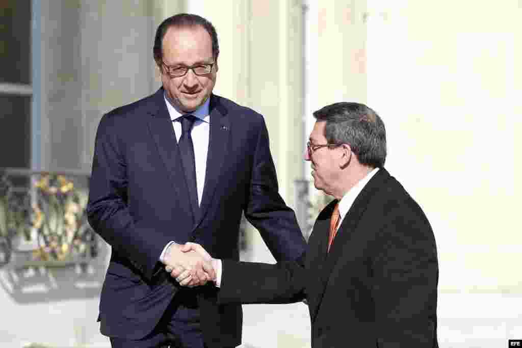 El presidente galo, François Hollande (izq), da la bienvenida al ministro de Exteriores cubano, Bruno Rodríguez (dcha), a su llegada al Palacio del Elíseo en París (Francia) hoy, martes 21 de abril de 2015. EFE/Yoan Valat