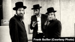 """Un hombre pasa frente a un anuncio en Brooklyn, NY. Fotografía del libro """"The Jews"""", cortesía de Frank Guiller."""
