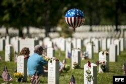 Varias personas visitan tumbas de familiares en el Cementerio Nacional de Arlington