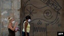 Dos mujeres caminan el martes por una calle de La Habana usando máscaras para evitar la propagación del coronavirus (Foto: Yamil Lage/AFP).