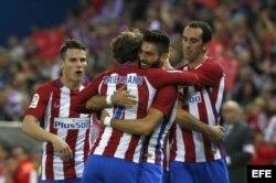 El delantero belga del Atlético de Madrid, Yannick Carrasco (2ºd), recibe la felicitación de sus compañeros tras marcar su tercer gol ante el Granada.