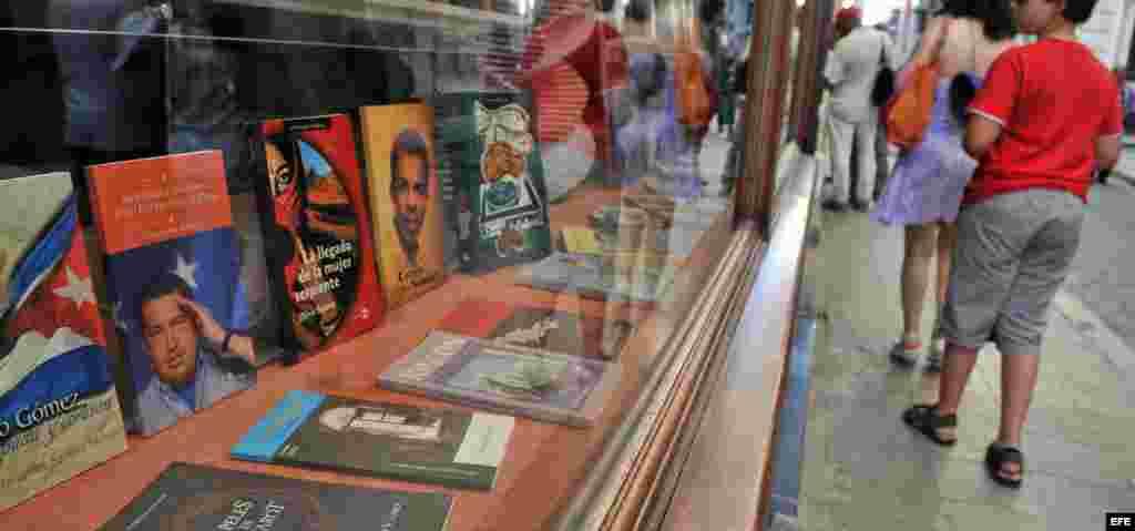 Varias personas pasan frente a una librería donde se expone un libro sobre el presidente de Venezuela, Hugo Chávez en La Habana.