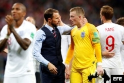 El técnico de Inglaterra Gareth Southgate (c-i) consuela al portero inglés Jordan Pickford (c-d) tras el partido Croacia-Inglaterra.