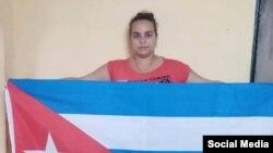 """Irina León Valladares, de la Fundación Vueltabajo por Cuba, portando el estandarte nacional bajo la campaña """"La bandera es de todos"""". (Facebook)."""