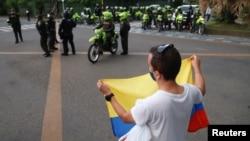 Un joven protesta frente a la policía antimotines en Cali, Colombia, este 9 de mayo. (REUTERS/Juan B Diaz)