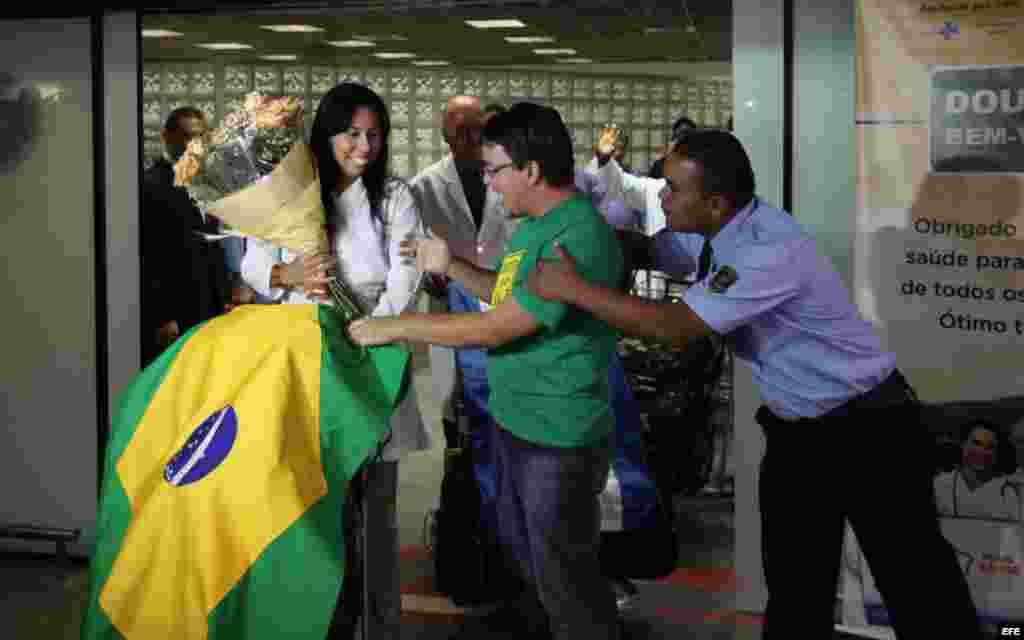 La médica cubana Yaisel Perea (i) es recibida por manifestantes que apoyan la llegada de doctores de Cuba al país, durante una recepción para un grupo de 200 profesionales hoy, sábado 24 de agosto de 2013, al aeropuerto de Brasilia. La presidenta brasile