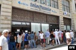 Varias personas hacen fila para ingresar a un telepunto y contratar el servicio de correo para sus teléfonos móviles en La Habana.