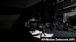 Una mujer con tapaboca cruza una calle en Caracas, el 26 de diciembre de 2021. [Foto: AP/Archivo]