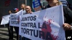 """Opositores al régimen de Nicolas Maduro en Venezuela portan un cartel que reza: """"Juntos contra la tortura"""", frente a la oficina de la ONU en Caracas."""