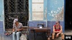 Un hombre repara zapatos, mientras otro vende una vieja máquina de coser en La Habana.