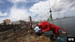 """Un león rojo creado por Roberto Favelo para la obra """"Garras en la piedra"""" instalado en los arrecifes del malecón de La Habana (Cuba)."""