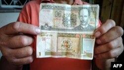 Un trabajador muestra un peso cubano (CUP) y un 1 CUC, que según la tasa oficial de cambio equivale a 25 CUP.