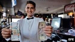 El mesero de un bar muestra billetes de 5 dólares y de 5 pesos cubanos convertibles en La Habana.