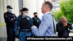 El abogado ruso Ivan Pavlov pasa junto a los agentes de policía para asistir a una sesión del tribunal después de hablar con los medios de comunicación en el Tribunal de Moscú en Moscú, Rusia, el 9 de junio de 2021. Foto: AP/Alexander Zemlianichenko.