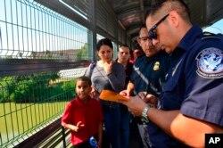 Funcionarios de Frontera procesan a una familia cubana en el Puente Internacional de Nuevo Laredo, Texas el 10 de julio de 2019 (Foto AP /Salvador González).