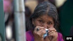 Una mujer espera los cuerpos de sus familiares, sepultados por un alud, en la morgue habilitada en Santa Catarina Pinula, Guatemala.
