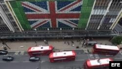 """Peatones caminan por Oxford Street donde se ha colocado una bandera británica en la fachada de unos grnades almacenes en Londres (Reino Unido) durante la jornada de referéndum por el """"Brexit"""" hoy, 23 de junio de 2016."""