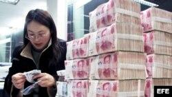 Una mujer cuenta billetes de banco chinos en una caja de ahorros de Hai'an, provincia de Jiangsu al este de China.