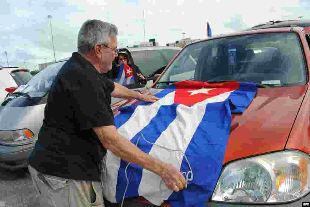 Un hombre coloca una bandera de cuba en su vehículo hoy, sábado 6 de junio de 2015, cuando unos 300 exiliados cubanos se concentraron en Miami.
