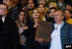 Flanqueada por el líder cívico de Santa Cruz Luis Fernando Camacho (a la derecha en la foto), la presidenta interina Jeanine Añez muestra una Biblia en la entrada del Palacio Quemado, residencia oficial del Ejecutivo boliviano (Foto: Aizar Raldes/AFP).