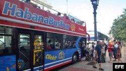 Turistas abordan un autobús turístico en La Habana.