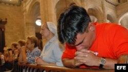 Varias personas participan en una misa en una iglesia católica en La Habana.