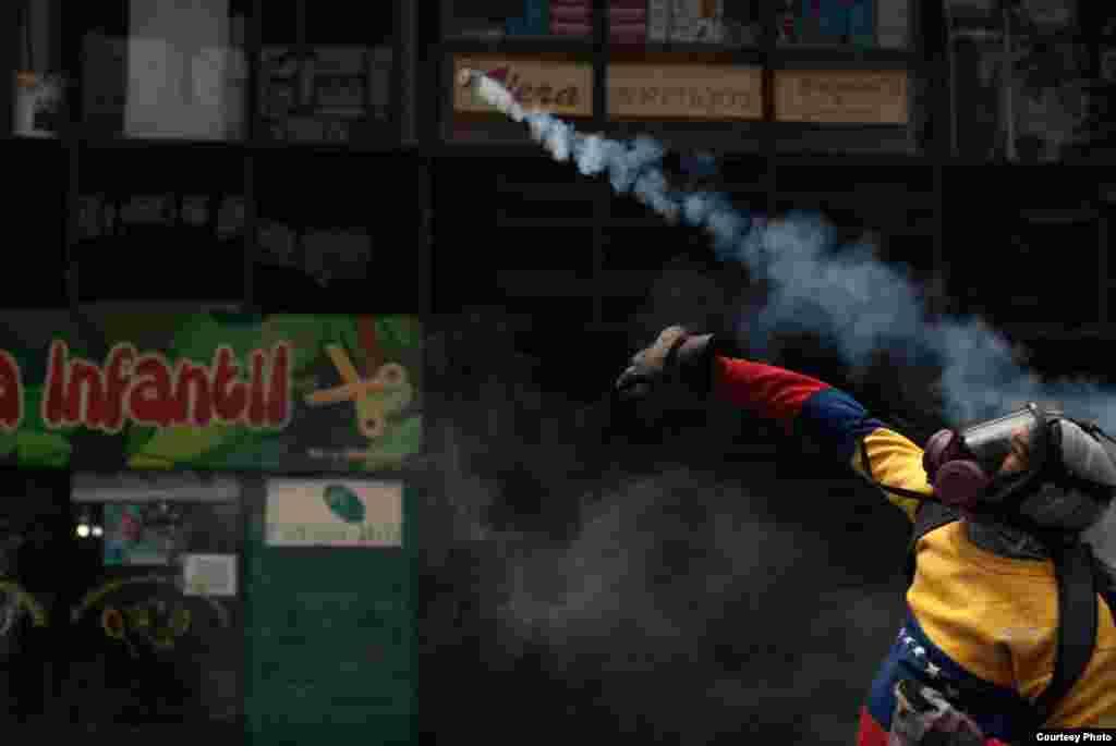 Encapuchado devuelve bomba lacrimógena lanzada por efectivos de la PNB. (Foto: Juan Pablo Arraez)