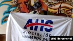 Artista cubano sotiene la bandera de la Asociación Hermanos Saíz.