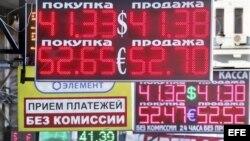 Varias personas caminan junto a un cartel que indica el cambio de divisa en Moscú, Rusia.