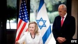 El presidente israelí Simón Peres (d) observa como la secretaria de Estado de EEUU Hillary Clinton (i) firma el libro de invitados durante una reunión en Jerusalén (Israel), hoy, lunes 16 de julio de 2012. EFE/ABIR SULTAN