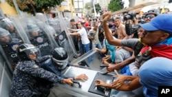 Miembros de la oposición venezolana se enfrentan a policías que impidieron el paso de una marcha en Caracas, Venezuela, el 10 de marzo del 2020.