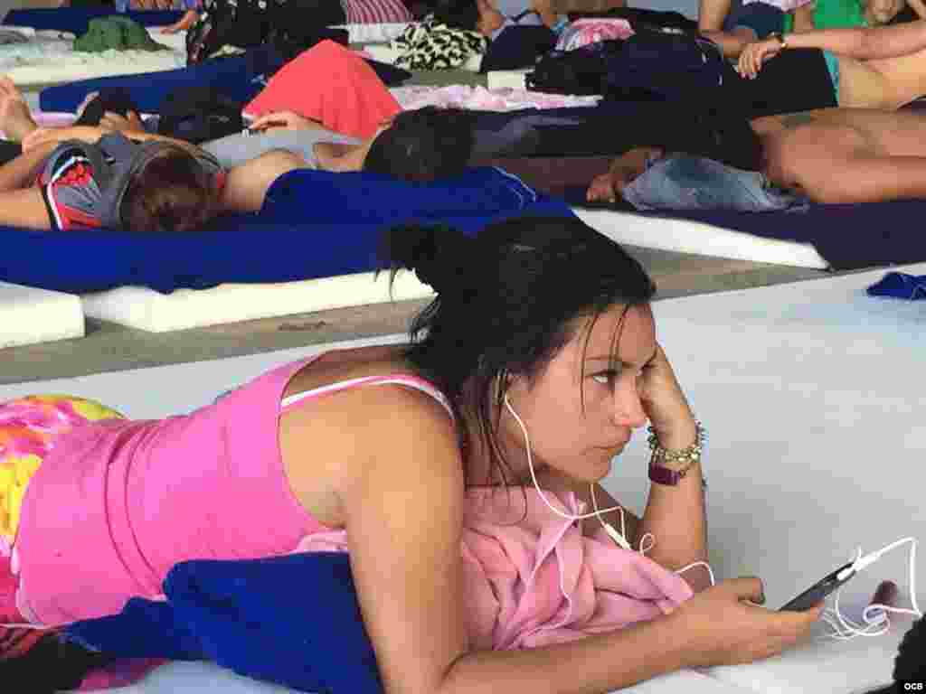 Atenta al celular en uno de los refugios para migrantes en Costa Rica.
