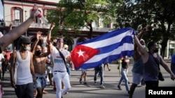 Manifestantes sostienen una bandera cubana durante las protestas del 11 de julio, en La Habana. (REUTERS/Alexandre Meneghini)