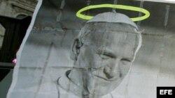 Archivo - Un peregrino sostiene un retrato del desaparecido Papa Juan Pablo II en una cola de miles de personas que intentan ver el cuerpo del Pontífice en la Basílica de San Pedro, de Roma.