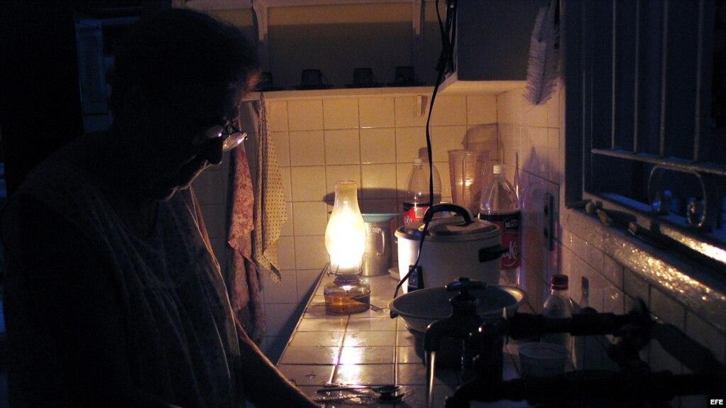 Una mujer lava los platos iluminada por una lámpara de queroseno durante un apagón