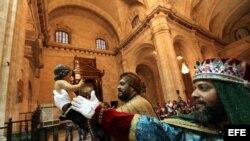 Foto archivo. Hombres disfrazados de Reyes Magos sostienen una imagen del Niño Jesús durante una ceremonia para celebrar la epifanía el 24 de diciembre de 2012, en la Catedral de La Habana (Cuba).