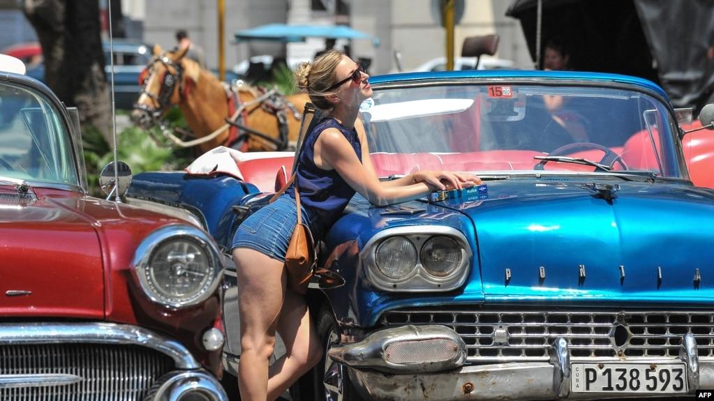 Una turista posa para una foto en La Habana Vieja. Al fondo, uno de los carruajes que pasean a los visitantes extranjeros.