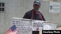 Llorente, con los carteles, listo para la protesta frente a la embajada de Cuba en Guyana.