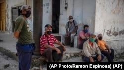 Trabajadores con sus máscaras esperan a las afueras de un central azucarero en Madruga, Cuba. (AP/Ramón Espinosa)