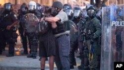 Policía abraza a uno de los manifestantes que ayudó a dispersar la multitud en Atlanta. AP Photo/John Bazemore