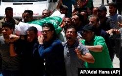 Dolientes cantan consignas islámicas mientras llevan el cuerpo de Awad Abu Selmiya, durante un funeral de trece militantes de Hamas frente a una mezquita en la ciudad de Gaza, el jueves 13 de mayo de 2021. Foto: AP/Adel Hana.