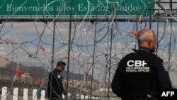 Miembros de la Patrulla Fronteriza de EEUU observan la instalación de las barreras de alambre de púas preparadas para la posible llegada masiva de migrantes al Puente Internacional de Zaragoza, en Ciudad Juárez, estado de Chihuahua, México.