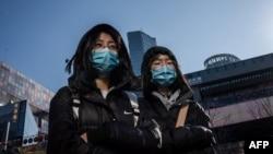 Transeúntes llevan máscaras el 23 de enero en un centro comercial de Pekín (Foto: Nicolas Asfouri/AFP).