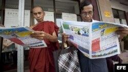 Dos hombres leen periódicos en Rangún (Birmania). Los estantes de los quioscos de Birmania amanecieron rebosantes gracias al regreso de los periódicos, con capital privado, a los puestos de venta.