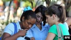 Jóvenes utilizan sus teléfonos celulares.