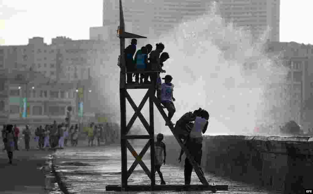 """Varios niños juegan en la obra """"Salvavidas"""" del artista Duvier Del Dago expuesta en el Malecón hoy, domingo 24 de mayo, donde ha sido inaugurada la exposición """"Detrás del Muro"""" como parte de la XII Bienal de Arte de La Habana."""