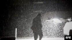 Un peatón camina el miércoles 7 de noviembre de 2012, por el distrito financiero de Manhattan, en Nueva York (EEUU), durante una tormenta de nieve.